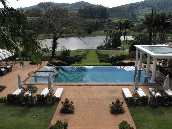 Vista a partir da casa, a piscina compõe com a paisagem da represa ao fundo, ligada à área de lazer pelo caminho ladeado de arbustos. Os pilares de sustentação da cobertura da churrasqueira parecem emergir da piscina