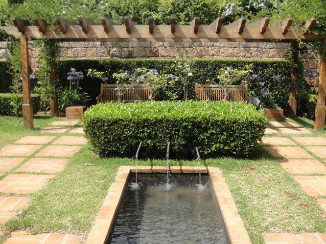 O caminho que ladeia o espelho d'água com bicas instaladas em meio ao arbusto do buxinho finaliza no canto do pergolado