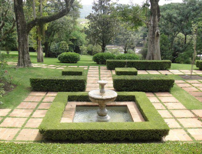 O novo jardim harmoniza-se a paisagem pré-existente como uma moldura das frondosas árvores. A rigidez do desenho simétrico em torno da fonte é quebrada pelo buxinho podado em linhas retas, ao fundo, deslocado para a direita, e os arbustos arredondados no gramado