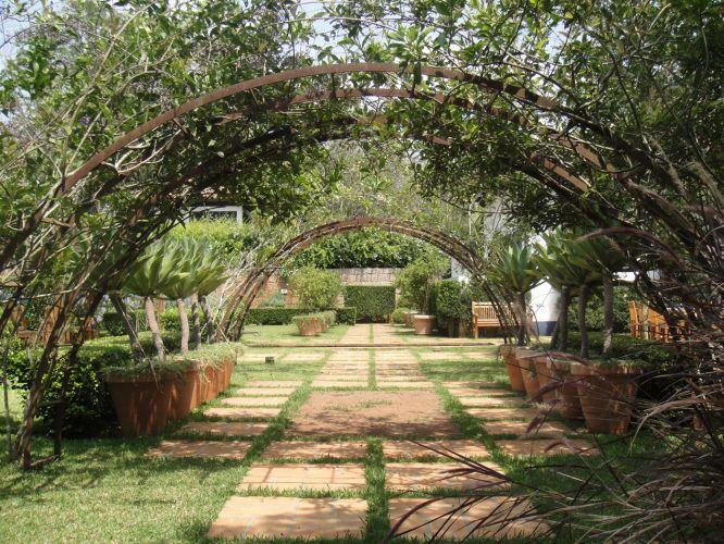 O pergolado em curva forma túneis que proporcionam um clima romântico à paisagem