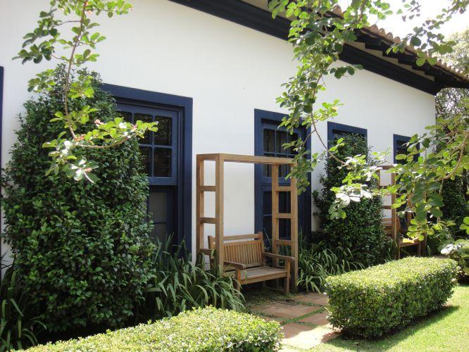 Dispostos entre os janelões da casa, os bancos de madeira protegidos por molduras pergoladas compõem áreas de descanso delimitada pela cerca de viburno