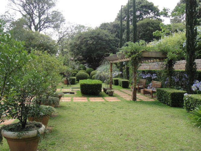 Toda a área do jardim é coberta de vegetação com apenas uma composição de tijolos marcando os caminhos. Ao fundo, as árvores altas nativas do terreno