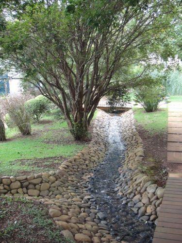 Revestindo o canal, seixos rolados também marcam a textura do jardim projetado por Gilberto Elkis em uma fazenda no interior de São Paulo