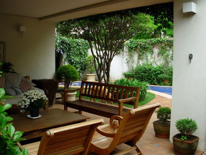 Vista da varanda da sala de estar, ambientada com móveis de madeira. Ao fundo, a jabuticabeira (Myrciaria cauliflora). Do muro pendem trepadeiras da espécie ipoméia (Ipomoea cairica) azul, à direita, e tumbérgia (Thumbergia), de flores lilás, à esquerda