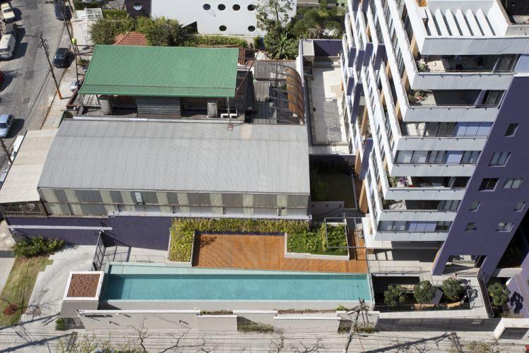 A implantação em L é simples, típica de bairros onde terrenos são estreitos; o bloco do edifício surge sobre área retangular