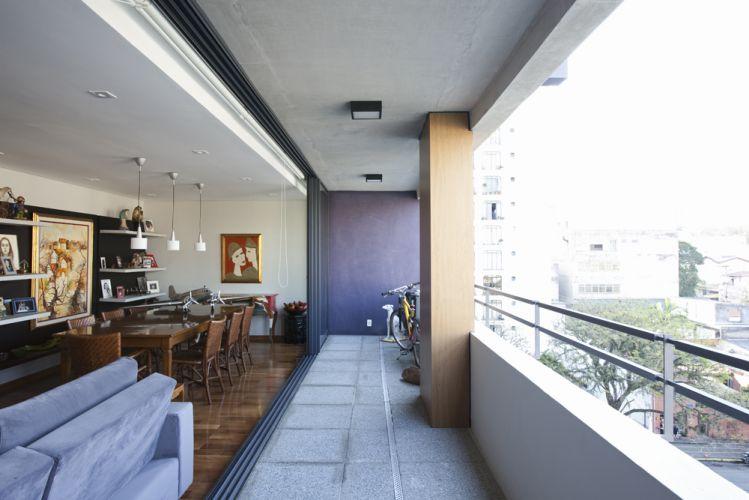 A decoradora manteve o piso de fulget da varandat. O terraço não tem móveis, pois a intenção do projeto é dar a ideia de que toda sala se transforma em área externa, quando as portas estão totalmente abertas
