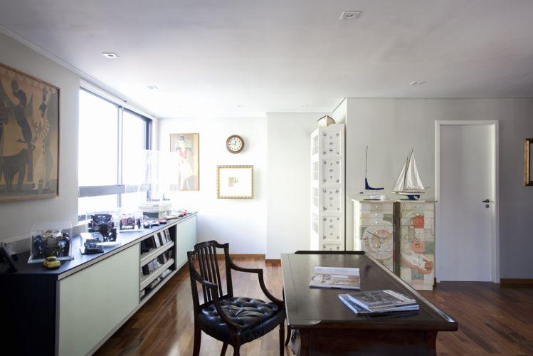 Uma mesa antiga de estudos tem lugar de destaque no escritório. Victoria Kertzer especificou o mesmo revestimento para piso dos dormitórios e das salas de estar e jantar. As cômodas pintadas foram feitas pela artista plástica Eliana Goes