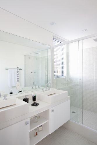 O piso do banheiro e as paredes do box são revestidos com pastilhas brancas, especificadas no projeto arquitetônico do edifício. Os armários de madeira foram projetados pela Marcenaria Artesanal