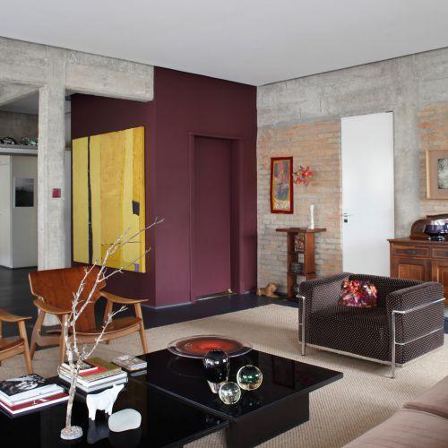 O volume do elevador pintado com tinta acrílica na cor vinho se destaca na entrada do apartamento reformado pelo arquiteto Gustavo Calazans. O quadro amarelo, do artista José Bernnô, promove o contraste de cores