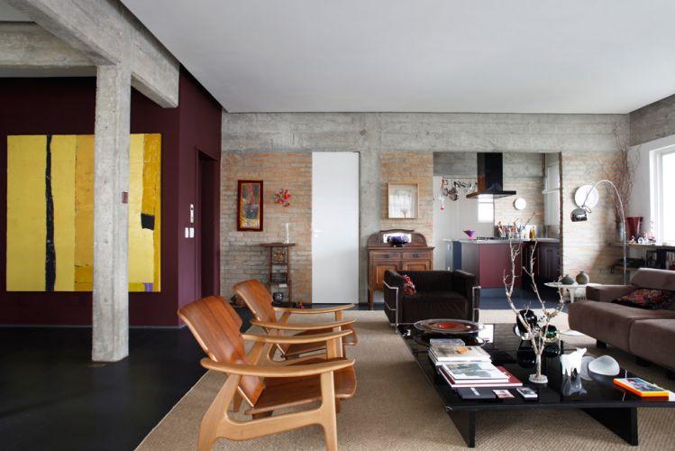 Vista da sala de estar com a cozinha integrada ao fundo, onde é possível ver a coifa Tuboar pintada com tinta eletrostática preta. No estar, luminária Pescador (da Arquivo Vivo Móveis), poltronas Diz (de Sergio Rodrigues, vendida na Dpot), poltrona Le Corbusier (da Clássica Design) e duas mesas Bonte (ao centro, da Arquivo Vivo Móveis)