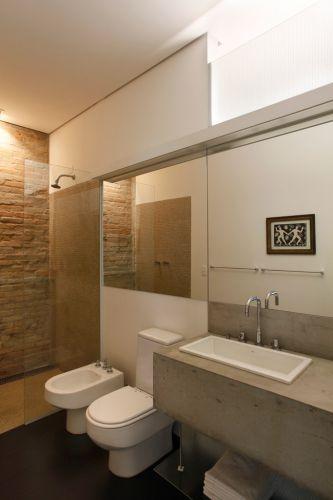 O banheiro da suíte também apresenta parede com tijolos descascados aparentes no fundo do box que possui ainda outra parede revestida com pastilhas de vidro, Vidrotil, transparente fumê. Combinando com o apartamento, a bancada é de concreto aparente com prateleira de vidro aramado. Cuba Deca