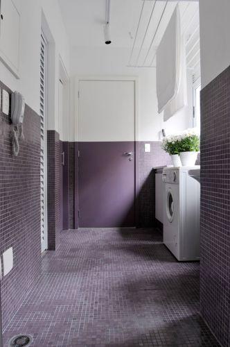 Na lavanderia, a porta foi pintada no mesmo tom de roxo das pastilhas da Vidrotil aplicadas no piso e meia parede. O objetivo foi dar continuidade visual ao espaço que integra o apartamento em São Paulo reformado por Guto Requena