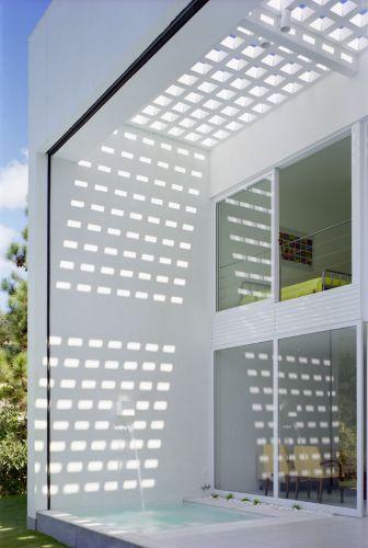 Detalhe da varanda mostra o spa com bica na parede e a cobertura pergolada que protege o local da insolação, além de imprimir um interessante efeito sobre a parece com sua sombra