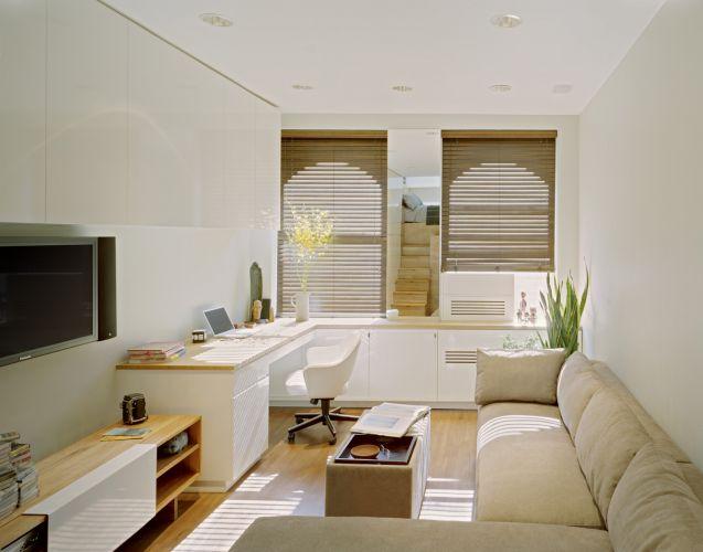 Vista do ambiente de estar e escritório do apartamento de 46 m² no East Village, em Nova York. A bancada com gabinetes oferece um confortável espaço de trabalho; o sofá contorna a porção oposta da sala e completa o retângulo formado em parte pela bancada e móvel da TV e som, estratégia que confere equilíbrio à ambientação