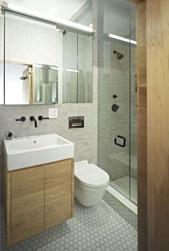 No banheiro foram empregados as mesmas diretrizes de projeto: revestimentos de cores neutras, madeira clara e um eficiente sistema de iluminação para compensar a falta de luz natural