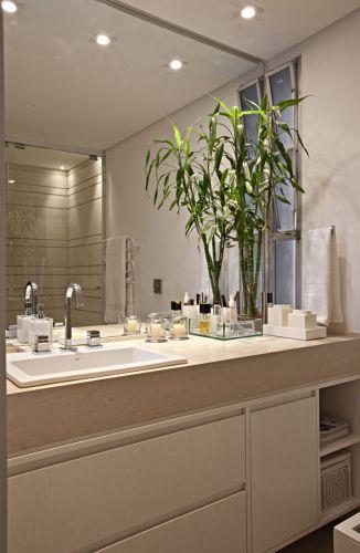 No banheiro da suíte, a bancada e as paredes do box são revestidas de limestone importado pela Mont Blanc Mármores e Granitos. No gabinete, carvalho americano laqueado pela Marcenaria AS