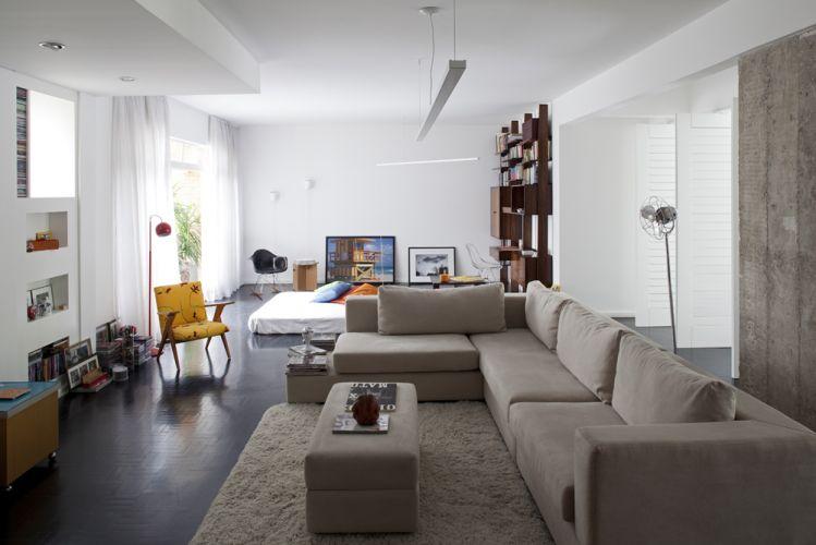 O living é dividido em dois ambientes: em primeiro plano, a sala de TV, com sofá em L; ao fundo, um recanto descontraído com um colchão almofadas coloridas divide espaço com a estante e escrivaninha
