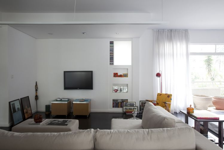 O espaço de televisão tem nichos na parede onde se organizam objetos e CDs. As fotos emolduradas dispostas sobre o piso são de Fran Parente. O living se abre para uma sacada