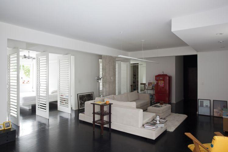 Livre da parede da circulação da área íntima, o living passou a receber luz natural através das portas pivotantes com venezianas (da Demuner) que dividem os quartos. As venezianas conferem um aspecto leve à composição