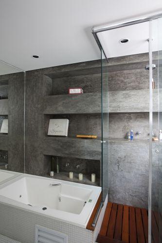 O banheiro da suíte máster é todo branco com revestimento de pastilhas Colormix. Destaque para a parede com tratamento diferenciado em cimento queimado
