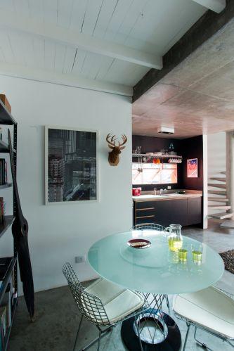 O canto reservado para a sala de jantar tem estantes comumente usadas em escritórios e até depósitos. Na parede, uma cabeça de veado feita de papelão, comprada nos Estados Unidos. No Brasil, é possível encontrar a peça na Artefacto Beach & Country. Sobre o aparador, uma bandeja com garrafas e uma luminária acrílica da Vírgula Ovo. A mesa Nogushi, da Tok & Stok, é complementada por cadeiras Bertoia