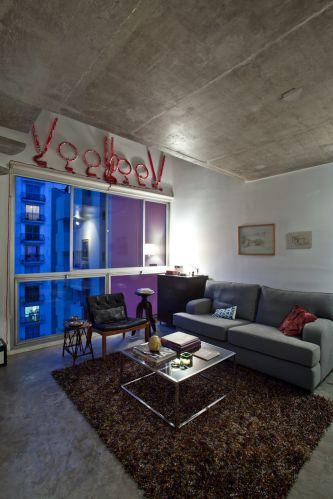 O sofá da sala é um modelo clássico, de linhas retas, trazido da casa dos pais do designer Marcel Steiner e forrado com sarja peletizada cinza. O tapete de nós sintéticos é um modelo Shaggy da By Kamy