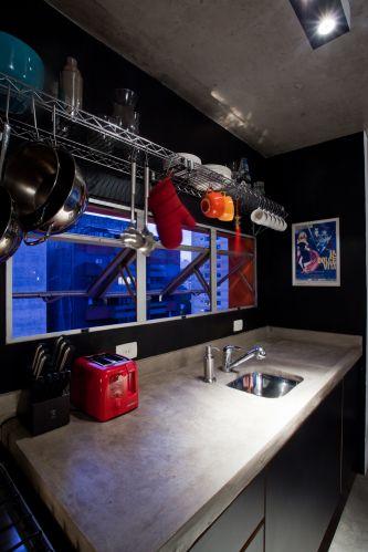 Na cozinha, parede e gabinete pretos. Sobre a janela, prateleiras industriais da Metal Stock para organizar louças, panelas e talheres. A bancada de concreto tem 2 m (largura) por 70 cm (profundidade). O tampo é mais fundo para que a pia sirva para apoiar eletrodomésticos e ainda sobrar espaço para preparar alimentos