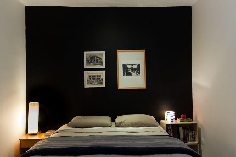 As paredes da suíte são pintadas de branco, exceto a que fica atrás da cama, que é preta. Marcel explica que escolheu essa cor para trazer aconchego ao ambiente e dar um acabamento à cama, que não possui cabeceira