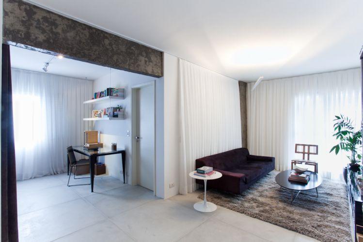 Ao ser recolhida, a cortina permite a integração do home-office ao estar e compõe elegante efeito junto ao sofá. Mesa de trabalho da Tok&Stok