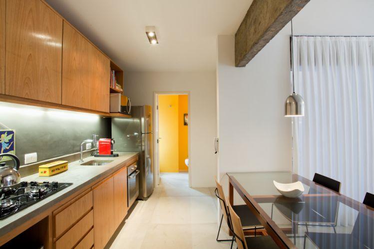 Encostada no pilar central, a mesa de jantar fica junto à cozinha, facilitando a rotina. Mesa e cadeiras de Fernando Jaeger