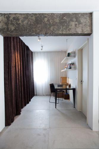De grande efeito cenográfico, as cortinas se destacam nesse espaço. Em veludo cotelê marrom, fazem o fechamento do closet e, em gaze de linho branca, pendem sobre a janela do ambiente, também utilizado como home-office. Iluminação pontual da Reka