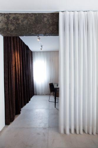 Detalhe do jogo de cortinas de efeito dramático junto à viga de concreto aparente. Piso em placas cimentícias da Solarium