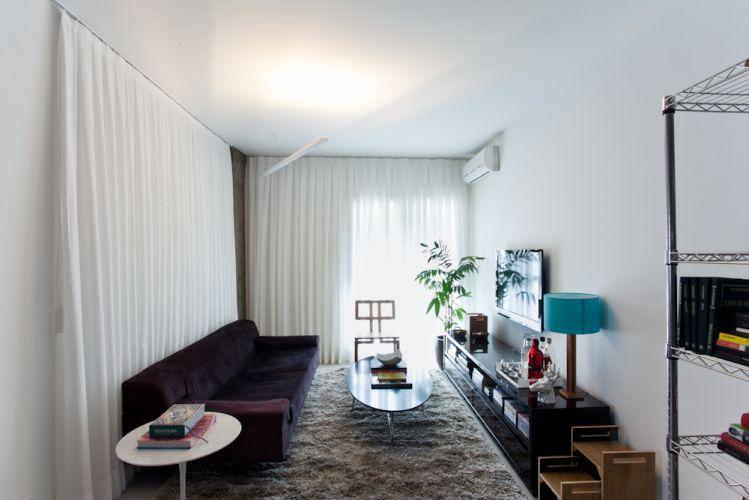 As cortinas brancas e a luz indireta da luminária Reka criam uma atmosfera suave para o estar, que possui bancada horizontal para guardar CDs e DVDs