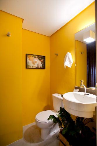 Contíguo à área de serviço e à cozinha, o lavabo recebeu pintura em tom mostarda
