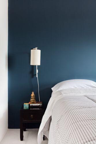 A parede pintada na cor petróleo, da Suvinil, concede suavidade ao dormitório do advogado, que tem criado-mudo antigo e luminária da Reka