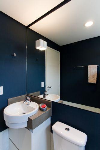 O mesmo tom petróleo aparece nas paredes do banheiro da suíte, em contraste com as louças brancas