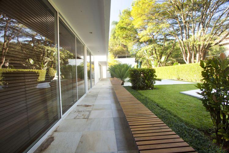No jardim de uma casa em São Paulo, o paisagista Marcelo Faisal instalou um banco de madeira sobre a mureta que também atua como guarda-corpo, frisando o limite do desnível. O elemento também ajuda a aumentar o jardim. A versátil grama preta (Ophiopogon japonicus) emoldura o gramado de esmeralda (Zoysia japônica) de onde despontam maciços de ixorias (Ixora chinensis)