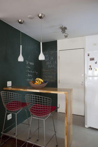 Os proprietários do apartamento, professores universitários, solicitaram aos arquitetos que preparassem alguma parede para ser usada como lousa. Foi escolhida uma quina localizada junto à entrada, na cozinha. A lousa foi executada com pintura de esmalte sintético fosco verde escolar (Suvinil)