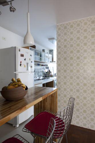 No apartamento projetado por Márcio Bariani e Alessandro Muzi não há portas separando as salas e a cozinha. A bancada (Marcenaria Pompéia) faz um pouco essa função, mas de maneira muito mais leve e aberta. A parede com azulejos decorados que antes fazia parte da cozinha original e foi mantida