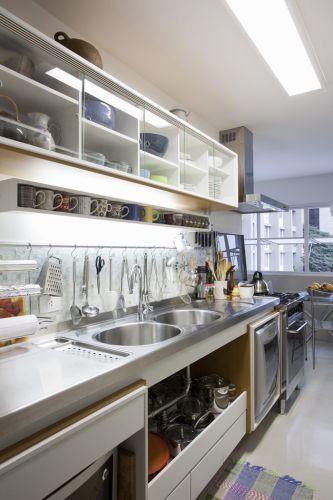 Era desejo dos proprietários que equipamentos e utensílios da cozinha ficassem à mostra. Os armários da cozinha foram especialmente desenhados para atender esse pedido, com nichos de diversos tamanhos, alguns com porta de vidro incolor e transparente. No piso, foi utilizado revestimento cimentício de alta aderência (NS Brazil). As cubas de aço inox são da Mekal
