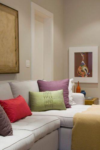 Detalhe do sofá do home theater, disponível no Emporio Vermeil. Sobre a base neutra do sofá e paredes acinzentadas, são as almofadas e a manta, do Empório Beraldin, as responsáveis pelo colorido da ambiente