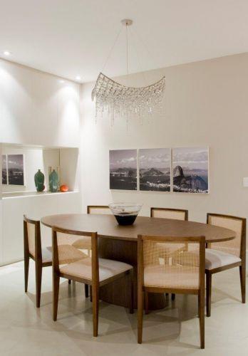 A sala de jantar tem a mesa oval em madeira da Empório Vermeil e cadeiras de palha para dar transparência. O lustre é da Scatto