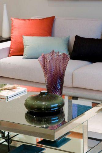 Com base de madeira e revestimento de espelhos, a mesa da Érea dá leveza e amplia a luz do espaço