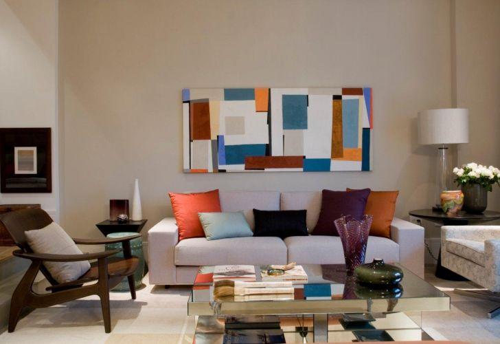 O colorido dos acessórios, como almofadas, manta e quadro dá vida ao ambiente de estar que tem sofá, paredes, piso em tonalidade neutra