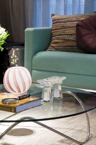 Detalhe da leveza da mesa de centro com tampo de vidro da Futton Company, contrastando com a poltrona verde claro do Empório Vermeil
