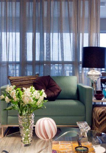 Do Empório Vermeil, a poltrona com forração de tecido verde claro tem dimensões generosas e oferece maior conforto aos moradores