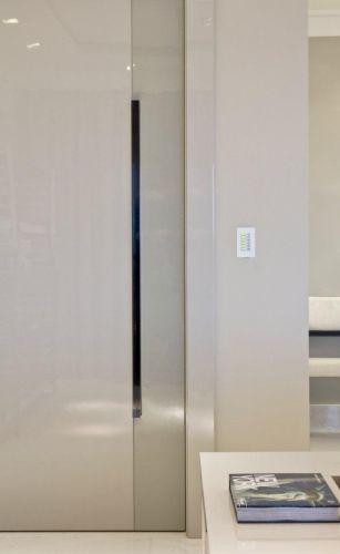 Pivotante, a porta de entrada foi executada pela Takae Arte com acabamento laqueado e puxador de acrílico