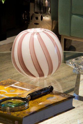 A mesa de centro acomoda vários objetos e livros, inclusive um vaso redondo de vidro, herança de família