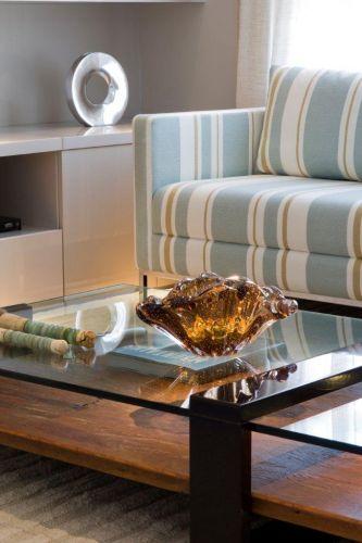 No home theater, mesa de centro com detalhe de vidro e madeira (da Brentwood). Sobre o móvel, vaso âmbar de murano da Tânia Bulhões