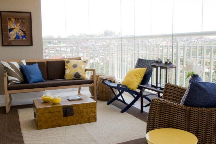 Esta é a sala externa, instalada na varanda. O sofá é da Casual Móveis, as almofadas e o banco amarelo, Empório Beraldin. Para complementar, tapete de fibra natural, da Fanucchi Tapetes. A varanda foi fechada com vidros e pode ser climatizada com ar-condicionado